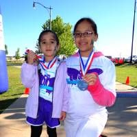 Photo - Showing off medals are Adamari Hernandez, 4, left, and her cousin, Edna Naomi Salazar, 12, first place winner of the Kiddie K part of the YWCA Oklahoma City's 2-Minute 5K. PHOTO BY TIFANNY M. POOLE, FOR THE OKLAHOMAN