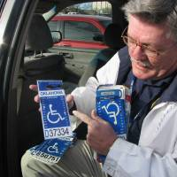 Photo - HANDICAPPED PARKING ENFORCEMENT / FAKE / FALSE: Handicap Parking Enforcement Specialist officer David Hoff holds bogus handicap parking placards he has confiscated BY VALLERY BROWN, THE OKLAHOMAN ORG XMIT: KOD