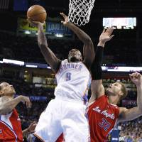 Photo - Oklahoma City Thunder forward Serge Ibaka (9) shoots between Los Angeles Clippers forwards Matt Barnes, left, and Blake Griffin (32) in the second quarter of an NBA basketball game in Oklahoma City, Wednesday, Nov. 21, 2012. Oklahoma City won in overtime, 117-111. (AP Photo/Sue Ogrocki) ORG XMIT: OKSO113