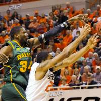 Photo - Baylor forward Cory Jefferson, left, reaches over Oklahoma State forward Michael Cobbins for a rebound during the first half of an NCAA college basketball game in Stillwater, Okla., Wednesday, Feb. 6, 2013. (AP Photo/Brody Schmidt)