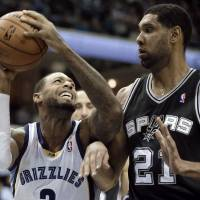 Photo - San Antonio Spurs' Tim Duncan (21), of U.S. Virgin Islands, defends against Memphis Grizzlies' James Johnson in the first half of an NBA basketball game in Memphis, Tenn., Tuesday, Jan. 7, 2014. (AP Photo/Danny Johnston)
