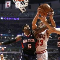 Photo - Chicago Bulls' Joakim Noah (13) struggles with Atlanta Hawks' Josh Smith and Kyle Korver (26) for a rebound during the first half of an NBA basketball game Monday, Jan. 14, 2013, in Chicago. (AP Photo/Charles Rex Arbogast)