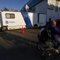 Photo -   A woman pedals her loaded tricycle past a Federal Emergency Management Agency trailer after receiving relief supplies from a clothing and food distribution center, Monday, Nov. 5, 2012, in Long Beach, N.Y. (AP Photo/Jason DeCrow)