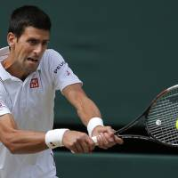 Photo - Novak Djokovic of Serbia plays a return to Roger Federer of Switzerland during their men's singles final at the All England Lawn Tennis Championships in Wimbledon, London, Sunday July 6, 2014. (AP Photo/Pavel Golovkin)