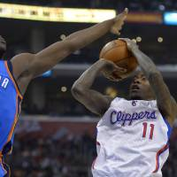 Photo - Los Angeles Clippers guard Jamal Crawford, right, puts up a shot as Oklahoma City Thunder guard Reggie Jackson defends during the first half of their NBA basketball game, Tuesday, Jan. 22, 2013, in Los Angeles.  (AP Photo/Mark J. Terrill) ORG XMIT: LAS102
