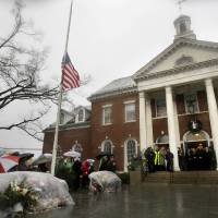 Photo - Officials including Connecticut Governor Dan Malloy observe a moment of silence on the steps of Edmond Town Hall while bells ring 26 times in Newtown, Conn., Friday, Dec. 21, 2012.   The chiming of bells reverberated throughout Newtown, commemorating one week since the crackle of gunfire in a schoolhouse killed 20 children and six adults in a massacre that has shaken the community and the nation. (AP Photo/Seth Wenig)