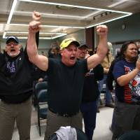 Photo - Boeing machinists react as the results of a vote are read at the International Association of Machinists union hall in Seattle on Wednesday, November 13, 2013. Boeing machinists in the Northwest rejected a contentious contract proposal Wednesday that would have exchanged concessions for decades of secure jobs. The International Association of Machinists District 751 announced Wednesday night that the proposal was rejected by 67 percent of the votes.  (AP Photo/seattlepi.com, Joshua Trujillo)