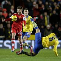 Photo - Southampton's Adam Lallana, left, competes for the ball with Arsenal's Mikel Arteta, right, during the English Premier League soccer match between Southampton and Arsenal at St Mary's stadium in Southampton, Tuesday, Jan. 28, 2014.  (AP Photo/Matt Dunham)
