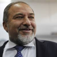 Photo - Israel's hard-line former Foreign Minister Avigdor Lieberman, arrives at a Jerusalem court for the opening hearing of his trial on charges of fraud and breach of trust, Sunday, Feb. 17, 2013. Lieberman is accused of trying to advance the career of a former diplomat who relayed information to him about a since-closed criminal investigation into his business dealings. (AP Photo/Ariel Schalit)