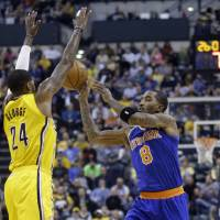 Photo - New York Knicks guard J.R. Smith, right, makes a pass over Indiana Pacers forward Paul George during the first half of an NBA basketball game in Indianapolis, Thursday, Jan. 16, 2014.  (AP Photo/Michael Conroy)
