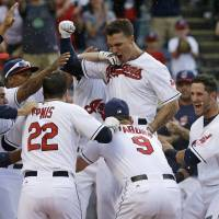 Photo - Cleveland Indians' Zack Walters, top, is mobbed by teammates after Walters hit a game-winning solo home run off Arizona Diamondbacks relief pitcher Randall Delgado in the ninth inning of the first baseball game of a doubleheader, Wednesday, Aug. 13, 2014, in Cleveland. The Indians defeated the Diamondbacks 3-2. (AP Photo/Tony Dejak)