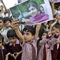 Photo -   A Pakistani boy holds up a picture of 14-year-old schoolgirl Malala Yousufzai, who was shot last Tuesday by the Taliban for speaking out in support of education for women, while he and other schoolchildren attend a protest condemning the attack, in Karachi, Pakistan, Saturday, Oct. 13, 2012. (AP Photo/Fareed Khan)