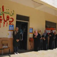 Photo -   Libyan voters line up at a polling station in Benghazi, Libya Saturday, July 7, 2012. Jubilant Libyans marked a major step toward democracy after decades of erratic one-man rule, voting Saturday in the first parliamentary election after last year's overthrow and killing of longtime dictator Moammar Gadhafi. But the joy over the historic vote was tempered by boycott calls, the burning of ballots and other violence in Libya's restive east. Arabic at left reads