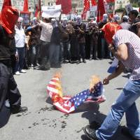 Photo -   Palestinians burn an American flag during a rally to demand better conditions for Palestinian prisoners in Israeli jails, in Nablus, West Bank, Saturday, May 12, 2012. (AP Photo/Nasser Ishtayeh)