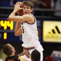 Photo - Kansas center Jeff Withey (5) rebounds over Oklahoma State guard Keiton Page (12) and passes to guard Tyshawn Taylor (10) during the first half of an NCAA college basketball game in Lawrence, Kan., Saturday, Feb. 11, 2012. (AP Photo/Orlin Wagner)  Orlin Wagner