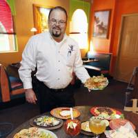 Photo - Chelino's owner Marcelino Garcia is surrounded by the food that has helped him open 13 locations in Oklahoma City.  Photo by Paul Hellstern, The Oklahoman  PAUL HELLSTERN - Oklahoman