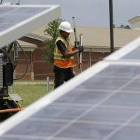 Photo - Manuel Gomes works to install solar panels in front of Dublin High School Tuesday, June 18, 2013, in Dublin, Ga. The solar panels being installed at the rural Georgia school are challenging one of its biggest electric monopolies. For years, Southern Co. subsidiary Georgia Power has claimed that no firm except itself can sell power in its state-designated territory. (AP Photo/John Bazemore)