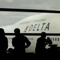 Photo - FILE - In this Monday, Oct. 29, 2012, file photo, travelers on Delta Airlines waits for flights, in Detroit. Delta said Superstorm Sandy hurt fourth-quarter profits by $100 million in 2012. That, plus special charges, left Delta Air Lines Inc. with a profit of just $7 million.  (AP Photo/Charlie Riedel, file)