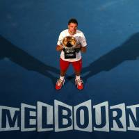 Photo - Stanislas Wawrinka of Switzerland holds the trophy after defeating Rafael Nadal of Spain in the men's singles final at the Australian Open tennis championship in Melbourne, Australia, Sunday, Jan. 26, 2014.(AP Photo/Eugene Hoshiko)