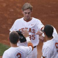 Photo - Texas' Madison Carter (35) celebrates with teammates after scoring a run  in the first inning of a second-round game against Oklahoma State in the Big 12 conference NCAA college baseball tournament in Oklahoma City, Thursday, May 22, 2014. (AP Photo/Alonzo Adams)