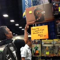 Photo - A man examines items for sale at Comic-Con in San Diego Sunday, July 21, 2013.  Comic-Con International and as the four-day   Comic-Con International  winds down Sunday, many vendors in the exhibition hall are cutting prices.   (AP Photo/Matt Moore)