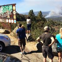Photo - People watch a fire burning from the Highway 41 overlook on the way north into Oakhurst, Calif., Monday, Aug. 18, 2014. The fire is burning north of the community. (AP Photo/The Fresno Bee, Eric Paul Zamora)