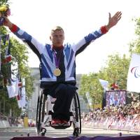 Photo -   Great Britain's David Weir celebrates on the podium with his gold medal after winning the men's marathon T54, at The Mall in London, with Buckingham Palace partially seen behind, Sunday Sept. 9, 2012. The man nicknamed the