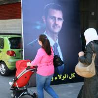 Photo - People walk by a campaign poster of the presidential elections for the incumbent President Bashar Assad in Damascus, Syria, Saturday, May 24, 2014. Assad's family has ruled Syria for more than 40 years. The June 3 vote will be the first time the family has faced challengers as opposed to a yes-or-no vote on their rule. (AP Photo)