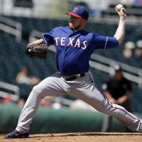 Photo - Texas Rangers' Robbie Ross throws during the first inning of a spring exhibition baseball game against the Cleveland Indians, Tuesday, March 25, 2014, in Goodyear, Ariz. (AP Photo/Darron Cummings)