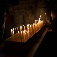 Photo - A Christian Catholic pilgrim lights a candle inside the Church of the Holy Sepulcher, traditionally believed to be the site of the crucifixion of Christ, in Jerusalem's Old City, Friday, March 29, 2013. Less than 2 percent of the population of Israel and the Palestinian territories is Christian, mostly split between Catholicism and Orthodox streams of Christianity. Christians in the West Bank wanting to attend services in Jerusalem must obtain permission from Israeli authorities. Israel's Tourism Ministry said it expects some 150,000 visitors in Israel during Easter week and the Jewish festival of Passover, which coincide this year. (AP Photo/Bernat Armangue)