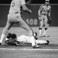 Photo - FILE - In this Sept. 8, 1981, file photo, Pete Rose, bottom, dives safely into third on a sacrifice by teammate Gary Matthews during early action against the Montreal Expos in Philadelphia, Pa. If Rose played today, his signature dives wouldn't be much of a novelty. It's become common in the majors for runners to fling their arms out, lead with their faces and hurtle toward bases. (AP Photo/Clem Murray, File)
