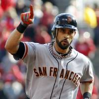 Photo -   San Francisco Giants' Angel Pagan gestures as he rounds the bases after hitting a solo home run against the Cincinnati Reds in the first inning of Game 4 of the National League division baseball series, Wednesday, Oct. 10, 2012, in Cincinnati. (AP Photo/David Kohl)