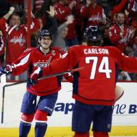 Photo - Washington Capitals right wing Alex Ovechkin (8), from Russia, celebrates his goal with defenseman John Carlson (74) in the first period of an NHL hockey game against the Los Angeles Kings, Tuesday, March 25, 2014, in Washington. (AP Photo/Alex Brandon)