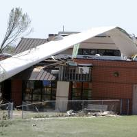 Photo - A blade used for fiberglass repair training rests on top of a daycare center at the Canadian Valley Technology Center in El Reno, Okla., after a tornado outbreak on May 31, 2013. The blade was anchored to the ground nearby and picked up by high winds. It did not come from a commercial wind turbine or training turbines at the CareerTech.  Aliki Dyer - The Oklahoman