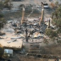 Photo - A charred vehicle sits near the remains of a destroyed home following a wildfire near Dunalley, east of the Tasmanian capital of Hobart, Australia, Saturday, Jan. 5, 2013.  Australian officials battled a series of wildfires amid scorching temperatures across the country on Saturday, with one blaze destroying dozens of homes in the island state of Tasmania. (AP Photo/Chris Kidd, Pool)