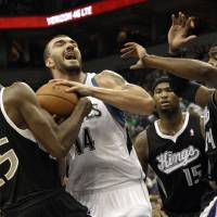 Photo -   Sacramento Kings' Travis Outlaw, left, tries to wrestle the ball away from Minnesota Timberwolves' Nikola Pekovic of Montenegro as he is surrounded by Kings players including Jason Thompson, right, and DeMarcus Cousins (15) in the first half of an NBA basketball game Friday, Nov. 2, 2012 in Minneapolis. (AP Photo/Jim Mone)