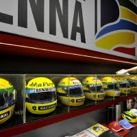 Photo - A man cleans helmets belonged to late Brazilian driver Ayrton Senna on display at the the Imola track, Italy, Wednesday, April 30, 2014. Fans and family members are gathering this week to pay their respects to former Formula One drivers Ayrton Senna and Roland Ratzenberger on the 20th anniversary of their deaths. F1 drivers' chaplain Sergio Mantovani celebrated a memorial mass Wednesday in a packed room beside pit lane at the Enzo and Dino Ferrari track that once hosted the San Marino Grand Prix. (AP Photo/Marco Vasini)