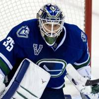 Photo - Vancouver Canucks goalie Cory Schneider (35) makes a save against the Calgary Flames during the second period of their NHL hockey game, Saturday, Feb. 9, 2013, in Vancouver, British Columbia. (AP Photo/The Canadian Press, Jonathan Hayward)