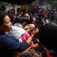 Photo - Daughter of Nepalese mountaineer Ang Kaji Sherpa, killed in an avalanche on Mount Everest, cries during the funeral ceremony in Katmandu, Nepal, Monday, April 21, 2014. Buddhist monks cremated the remains of Sherpa guides who were buried in the deadliest avalanche ever recorded on Mount Everest, a disaster that has prompted calls for a climbing boycott by Nepal's ethnic Sherpa community. The avalanche killed at least 13 Sherpas. Three other Sherpas remain missing and are presumed dead. (AP Photo/Niranjan Shrestha)