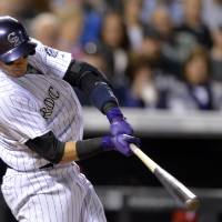 Photo - Colorado Rockies' Troy Tulowitzki hits an RBI-single off Philadelphia Phillies relief pitcher Mario Hollands during the sixth inning of a baseball game on Friday, April 18, 2014, in Denver. (AP Photo/Jack Dempsey)