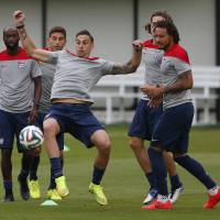 Photo - United States' Geoff Cameron attempts to keep a ball in the air as teammates look on during a training session at the Sao Paulo FC training center in Sao Paulo, Brazil, Monday, June 9, 2014. The U.S. will play in group G of the 2014 soccer World Cup. (AP Photo/Julio Cortez)