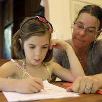 """Photo - Stacey Jacobson-Francis works on math homework with her 6 year old daughter Luci Wednesday, May 14, 2014, at their home in Berkeley, Calif. As schools around the U.S. implement national Common Core learning standards, parents trying to help their kids with math homework say that adding, subtracting, multiplying and dividing has become as complicated as calculus.  Stacey Jacobson-Francis, 41, of Berkeley, California, said her daughter's homework requires her to know four different ways to add. """"That is way too much to ask of a first grader. She can't remember them all, and I don't know them all, so we just do the best that we can,"""" she said. (AP Photo)"""