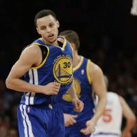 Photo - Golden State Warriors' Stephen Curry reacts after scoring during the first half of an NBA basketball game against the New York Knicks, Wednesday, Feb. 27, 2013, in New York. (AP Photo/Frank Franklin II)