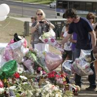 Photo -   Actor Christian Bale, second right, and his wife Sibi Blazic, right, place flowers on a memorial to the victims of Friday's mass shooting, Tuesday, July 24, 2012, in Aurora, Colo. Twelve people were killed when a gunman opened fire during a late-night showing of the movie Dark Knight Rises, which stars Bale as Batman. (AP Photo/Ted S. Warren)