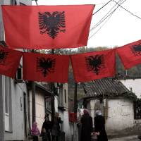 Photo -   In this photo taken Friday, Nov. 23, 2012, people walk through a small street decorated with Albanian flags, in Skopje, Macedonia. Macedonian capital Skopje, particularly the parts populated with ethnic Albanians, are flooded with Albanian flags, in the eve of the celebration of 100 years of Albania's independence and the national flag. Ethnic Albanians make up a quarter of Macedonia's 2.1 million people and are the largest ethnic minority in the country. (AP Photo/Boris Grdanoski)
