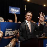 Photo - David Perdue waves to supporters after declaring victory in the Republican primary runoff for nomination to the U.S. Senate from Georgia, at his election-night party in Atlanta, Tuesday, July 22, 2014. Perdue defeated Rep. Jack Kingston. (AP Photo)