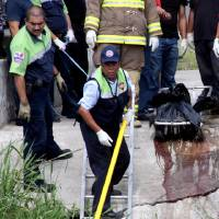 Photo -   Police remove from a canal, plastic bags containing the dismembered bodies of four people, in Boca del Rio, Mexico, Thursday, May 3, 2012. The bodies were found dumped together in plastic bags by a canal in the eastern Mexican state of Veracruz on Thursday, less than a week after the killing of a reporter for an investigative newsmagazine. At least three of the slain had worked as news photographers. (AP Photo/Felix Marquez)