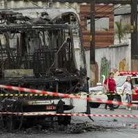 Photo -   A torched commuter bus is surrounded by police tape in a suburb of Sao Paulo, Brazil, Monday, Nov. 12, 2012. Bus burnings were part of a wave of violence that left 31 dead over the weekend in Sao Paulo, according to police. (AP Photo/Andre Penner)