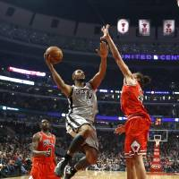 Photo - San Antonio Spurs center Boris Diaw (33) shoots over Chicago Bulls center Joakim Noah (13) as forward Luol Deng watches during the first half of an NBA basketball game, Monday, Feb. 11, 2013, in Chicago. (AP Photo/Charles Rex Arbogast)