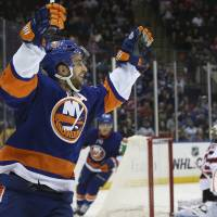 Photo - New York Islanders center Frans Nielsen (51) celebrates after scoring in the second period of an NHL hockey game against the New Jersey Devils, Saturday, March 29, 2014, in Uniondale, N.Y. (AP Photo/John Minchillo)